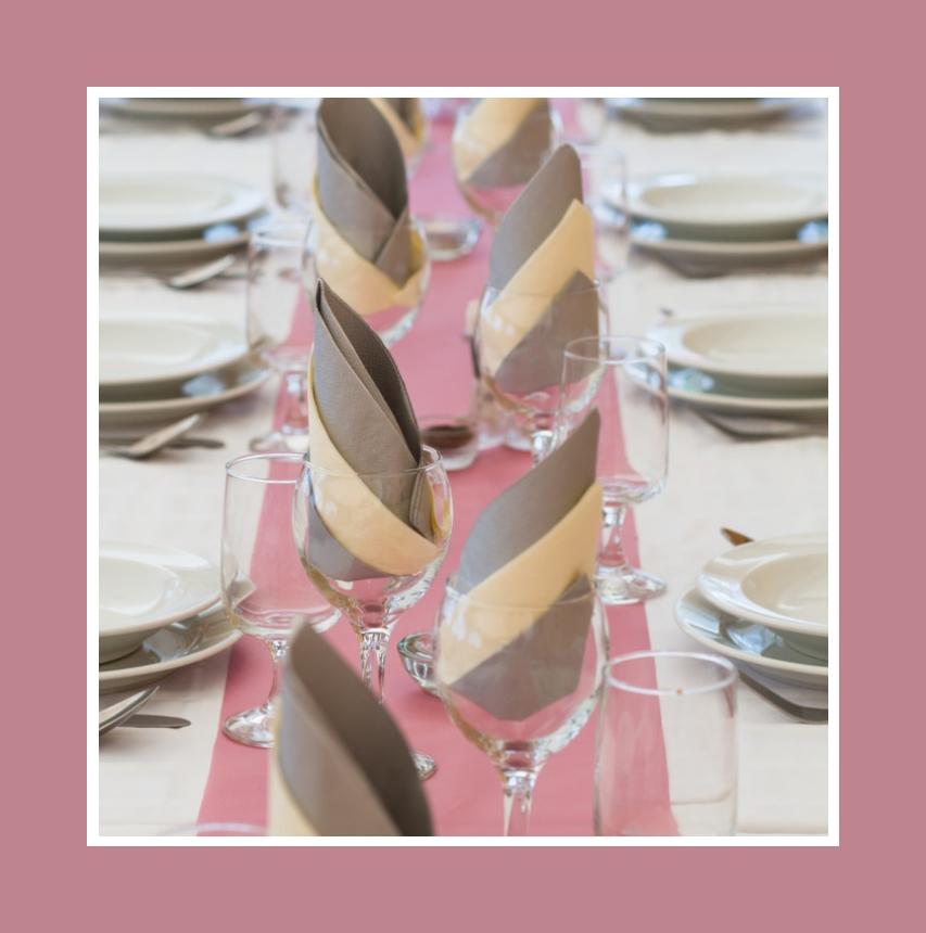 Beigefarbene und braun-graue Servietten auf einem rosa Tischläufer