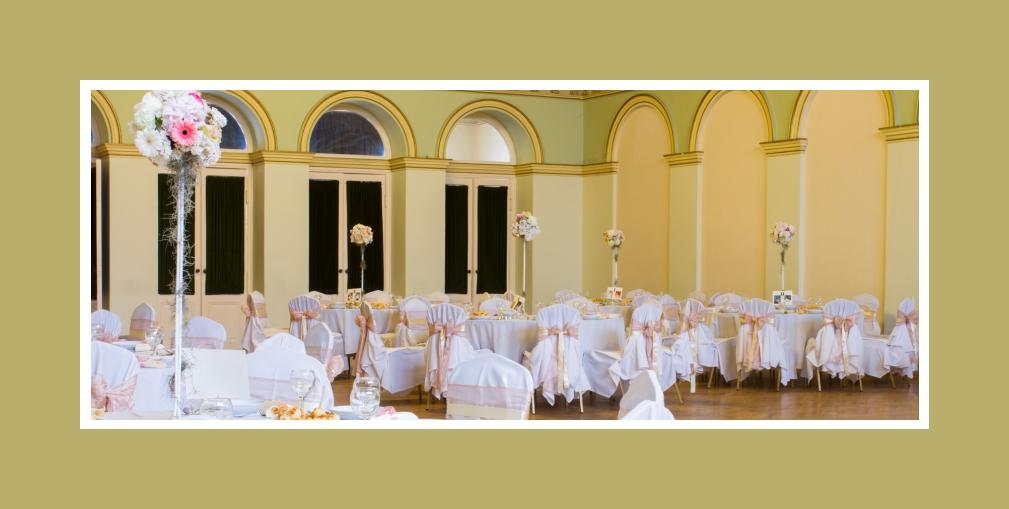 Pfirsichfarbene Hochzeitsdeko in gleichfarbener Halle mit grünen Elementen