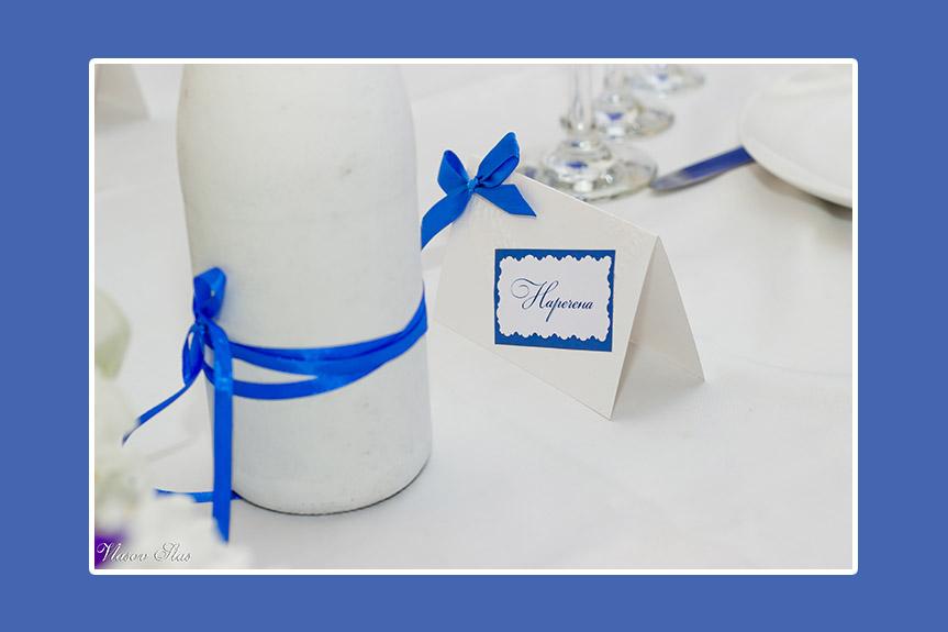 Blaue Schleifen auf weißem Brautpaartisch