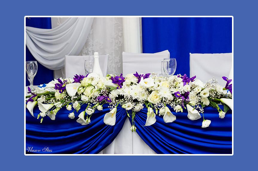 Hochzeitstafel mit blauem Satin und weißen Blumen