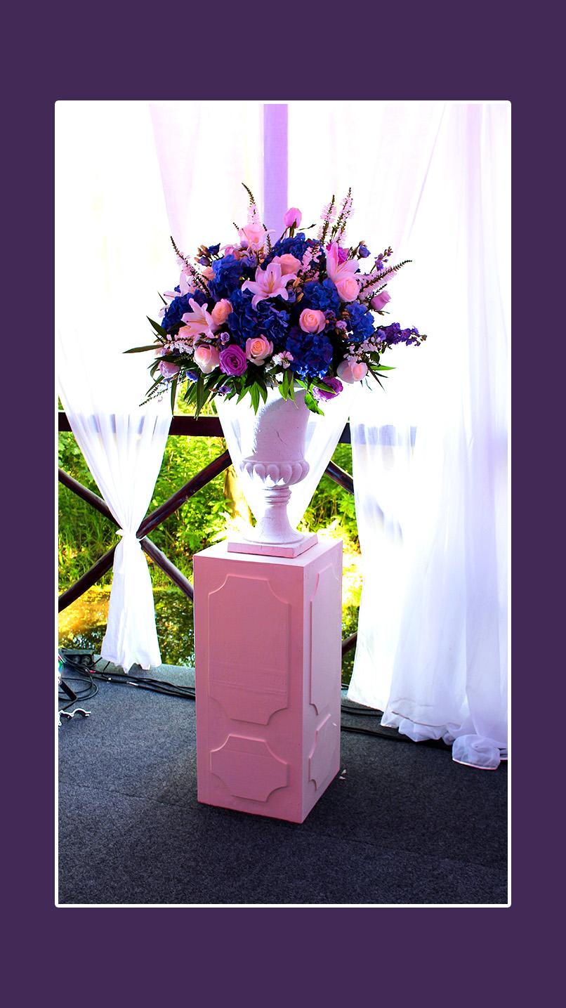 Rosen, Hortenseien, Lilien auf Säulen neben dem Brautpaartisch