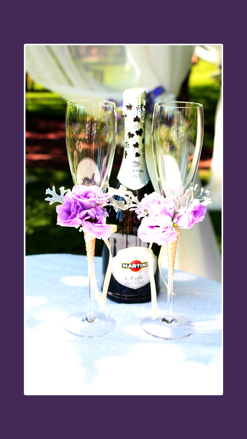 Violette Blumendeko auf Hochzeitsgläsern